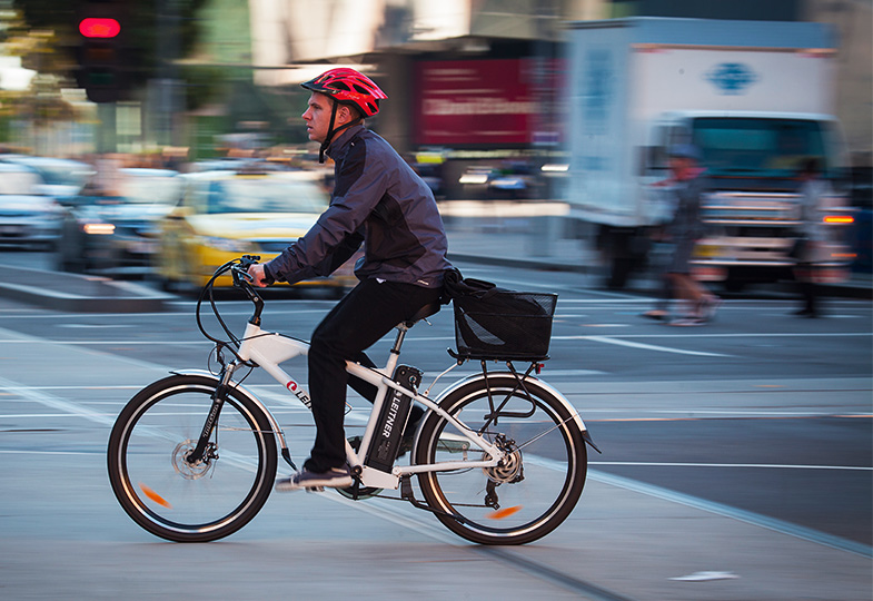 A cyclist riding through Melbourne's CBD.