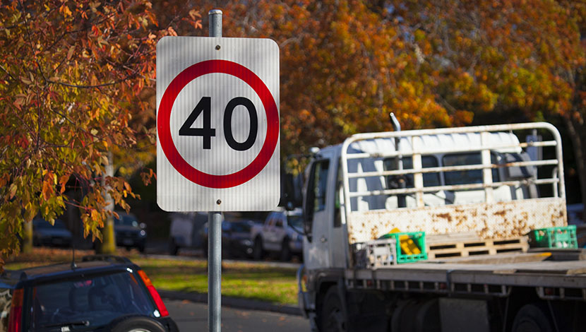 Truck driving past speed sign